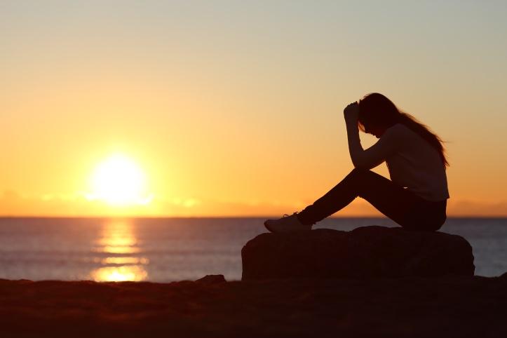 Sad woman silhouette worried on the beach