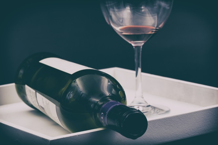 wine glass and wine bottle lying on its side